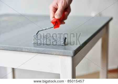 Painting a table using paint roller
