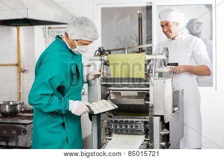 Male chefs preparing ravioli pasta in machine at commercial kitchen