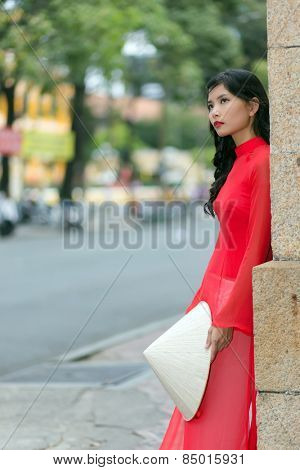Gorgeous girl in traditional Vietnamese clothing standing leaning against a brick wall in an urban street staring dreamily up into the air, side view