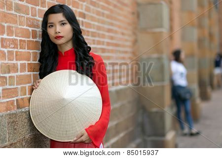 Attractive young Vietnamese woman wearing traditional clothing holding her hat in front of her as she leans against a brick building in an urban street looking at the camera
