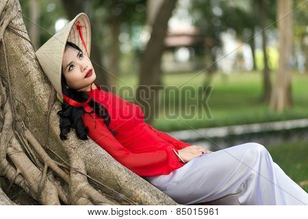 Gorgeous young Vietnamese woman dressed in a traditional red outfit daydreaming as she leans comfortably back against the trunk of tree in an urban park