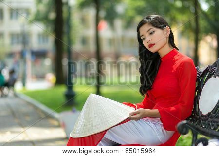 Sad young Vietnamese woman in traditional red clothing sitting on a bench in an urban park with her hat on her knee staring at the ground