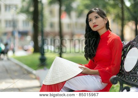 Gorgeous slender young Asian woman in red traditional Vietnamese clothing sitting daydreaming on a park bench in a town