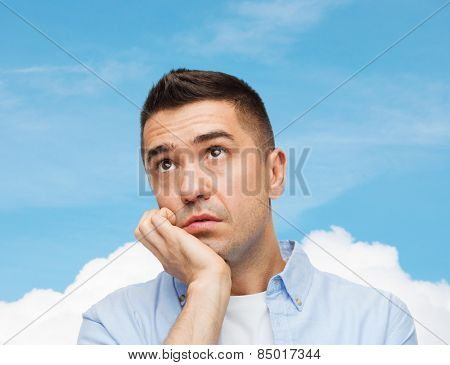 emotions and people concept - sad middle aged man over blue sky and cloud background