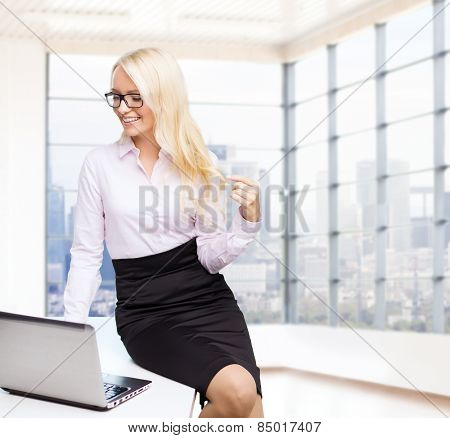 education, business, flirting and technology concept - smiling businesswoman or secretary with laptop computer sitting on table over office room with city view window background
