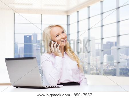 business, communication, people and technology concept - smiling businesswoman or secretary with laptop computer calling on smartphone over office room with city view window background