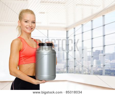 sport, fitness, food additive and people concept - smiling young woman holding protein jar over gym or home background