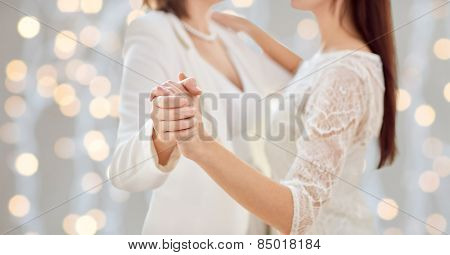 people, homosexuality, same-sex marriage and love concept - close up of happy married lesbian couple dancing over holiday lights background