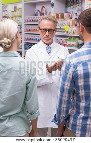 Senior pharmacist explaining the pills to patient at pharmacy