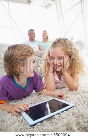 Happy brother and sister with digital tablet on rug at home