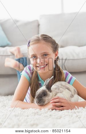 Full length portrait of smiling girl with rabbit lying on rug in living room