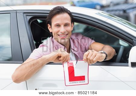 Learner driver smiling and tearing l plate in his car