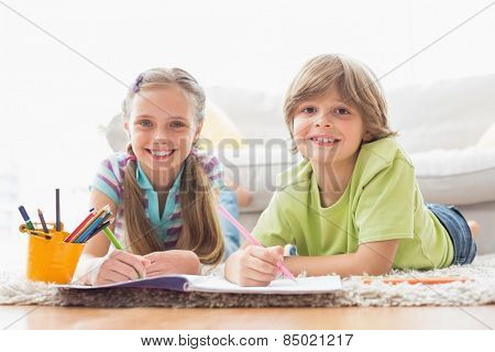Portrait of happy siblings drawing while lying on rug at home in the living room