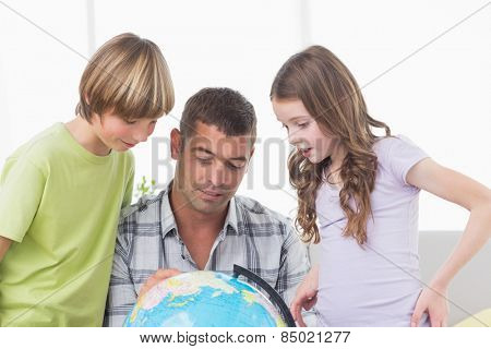 Siblings with father exploring map on globe at home
