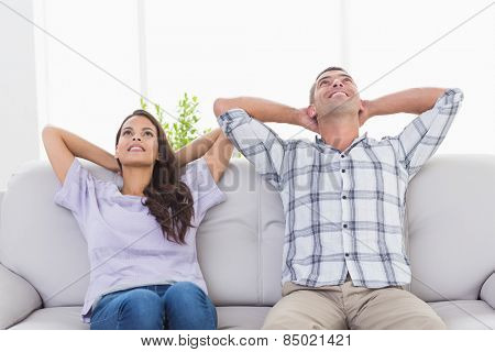 Thoughtful happy couple with hands behind head sitting on sofa at home