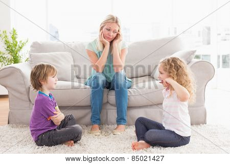 Upset mother looking at children fighting on rug at home