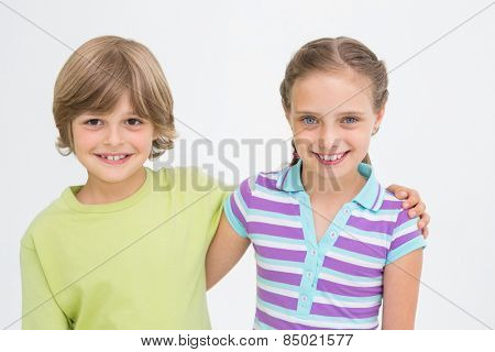 Portrait of cute siblings standing arm around on white background