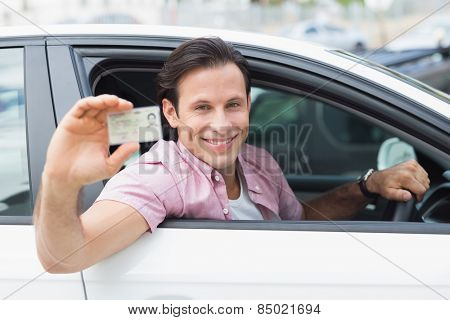 Man smiling and holding his driving license in his car