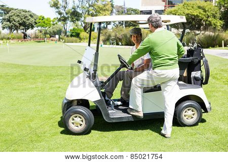 Happy golfing friends setting out on buggy at golf course