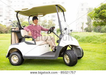 Golfer driving his golf buggy looking at camera at the golf course