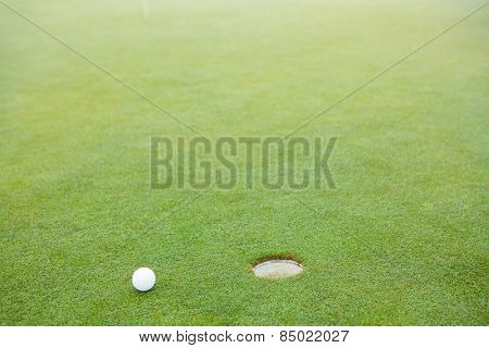 Golf ball next to hole at the golf course