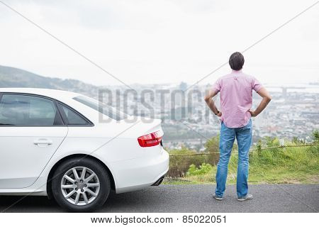 Man looking at the view near his car at the side of the road