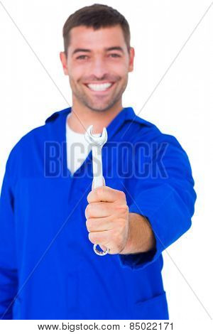 Portrait of smiling male mechanic showing spanner on white background