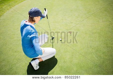 Focused lady golfer kneeling on the putting green on a sunny day at the golf course