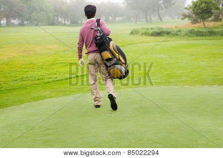 Golfer walking away holding golf bag at golf course