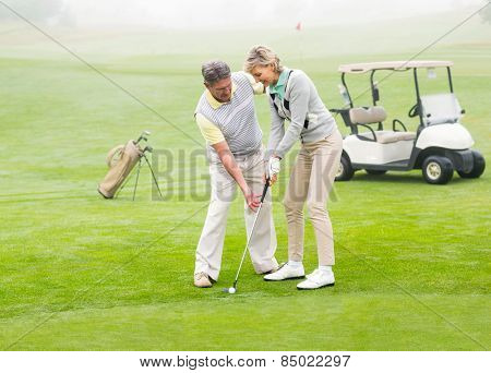 Golfing couple putting ball together on a foggy day at the golf course
