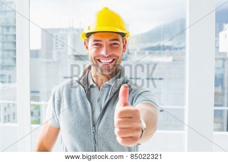 Portrait of smiling manual worker gesturing thumbs up in building