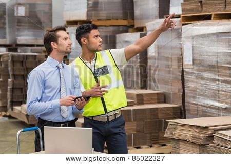 Warehouse worker showing something to his manager in a large warehouse