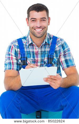 Portrait of happy plumber writing on clipboard while sitting on toolbox over white background
