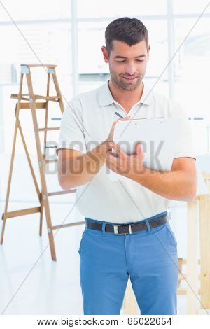 Male handyman writing on clipboard at construction site
