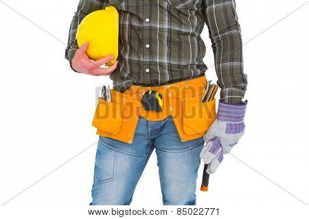 Manual worker wearing tool belt while holding gloves and helmet on white background