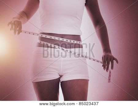 Midsection of woman measuring waist against grey