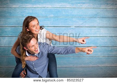 Smiling young man carrying woman against wooden planks