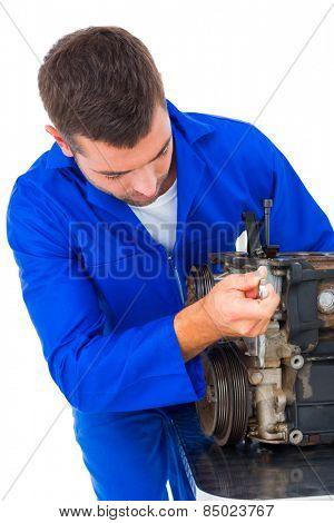 Male mechanic repairing car engine on white background