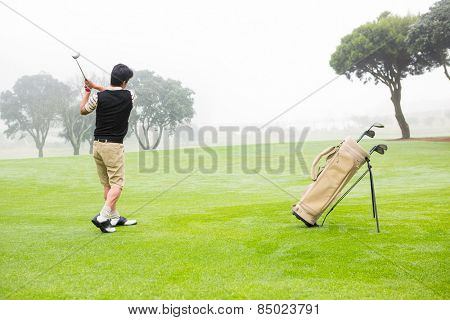 Golfer teeing off at the golf course