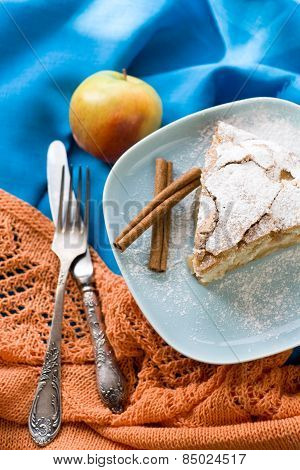 A Piece Of Apple Pie Lying On Blue Plate, Apple, Cinnamon Sticks, Forks On A Color Background