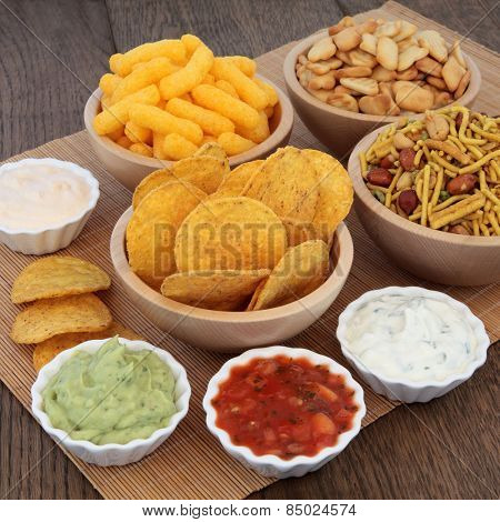 Crisp and dip party food selection in porcelain and wooden  bowls.