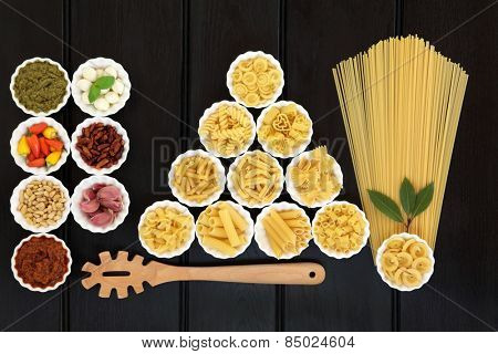 Italian pasta and mediterranean food ingredients in porcelain bowls over dark wood background.
