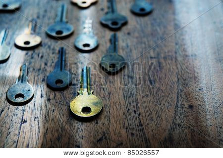 Grungy brass keys aligned in on a old wooden desk. Security and encryption concept image. Shallow depth of field. Focus is on forehand gold key. Intentionally shot in surreal color.