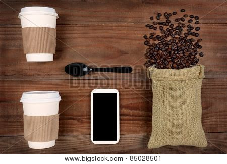 high angle shot of take-out coffee cups and a burlap bag with beans spilling out on a rustic wood table. A cell phone and spoon in the middle with copy space, Horizontal Format.