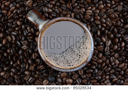High angle shot of a coffee mug surrounded by fresh roasted beans.