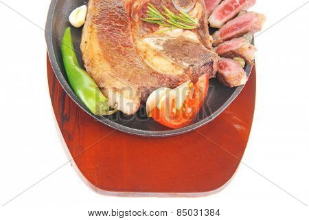 fresh grilled beef meat fillet on metal iron pan with tomatoes and red pepper isolated on white background