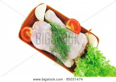 raw drumstick with lettuce and tomatoes over white