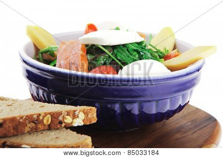 green salad with salmon and tomatoes on wood