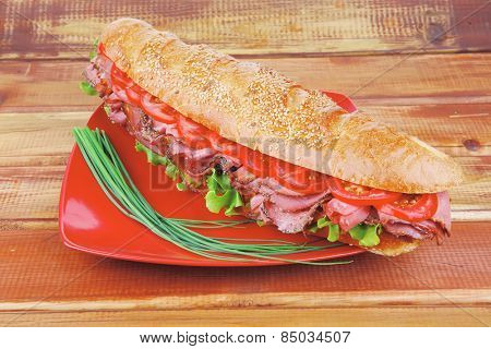 french sandwich on red plate : baguette with smoked sausage over wooden table