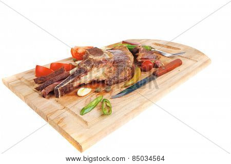 fresh roasted beef meat steak sliced on wooden board with red hot pepper cutlery isolated  over white background